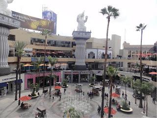 Rund, åpen plass med fontene i midten. Butikker og kafeer i flere etasjer rundt plassen. Høye palmer og elefantskulpturer dekorerer plassen.