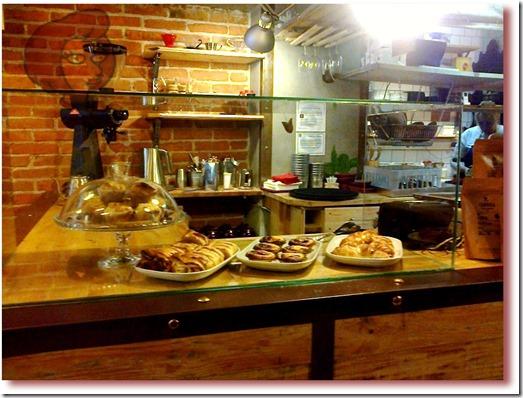 """Foto do balcão da """"Fábrica - Coffee Roasters"""" com muffins, croissants, pastéis de nata e outros itens de pastelaria"""