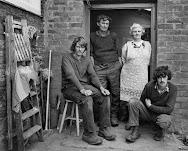 gezin op erf: man en vrouw leunend tegen deurpost, 2 zonen ervoor zittend