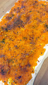 Topping of cream cheese and squash for a Squash Pinwheel, further sprinkled by various spices and seasonings to taste