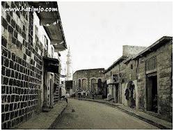 شارع خان حدو على يمين الصورة خان حدو كان مكان لوجود الخيل فيه للمبيت ويعمل للخيل حذوه والجهه اليسار من الصورة محلات لصباغه الجواعد وبيعها والان اصبح سوق الصاغه