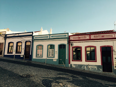 3 små, like hus i ulike farger.