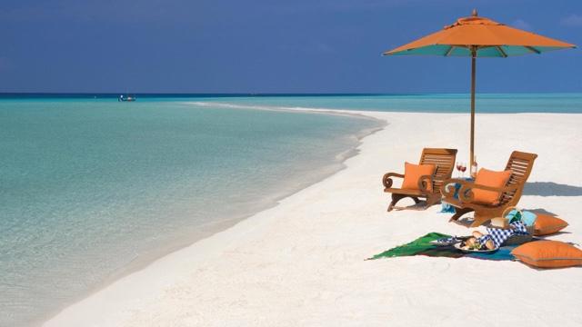 kursi santai, tikar dan makanan di tepi pantai