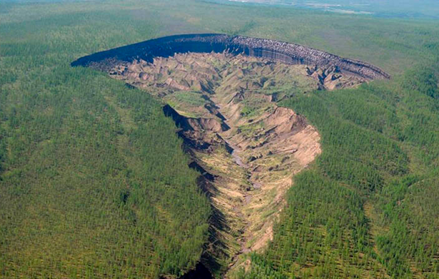Aerial view of the Batagaika Crater in Siberia. The ominous crater is a thermokarst so large that it's called a 'megaslump'. It looms a mile long and reaches depths of nearly 400 feet. It appeared without warning some 25 years ago. According to geological surveys, it's been growing at an annual rate of more than 60 feet. Photo: Research Institute of Applied Ecology of the North / Alexander Gabyshev