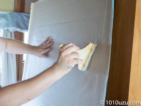 壁紙を刷毛でなでて空気を抜く