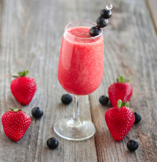 photo of a glass of Strawberry Champagne garnishes with blueberries