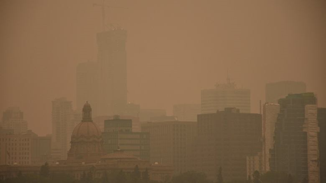 Smoke from wildfires in British Columbia cause hazy conditions that cast a strange hue over downtown Edmonton on Wednesday morning, 15 August 2018. Photo: Terry Reith / CBC