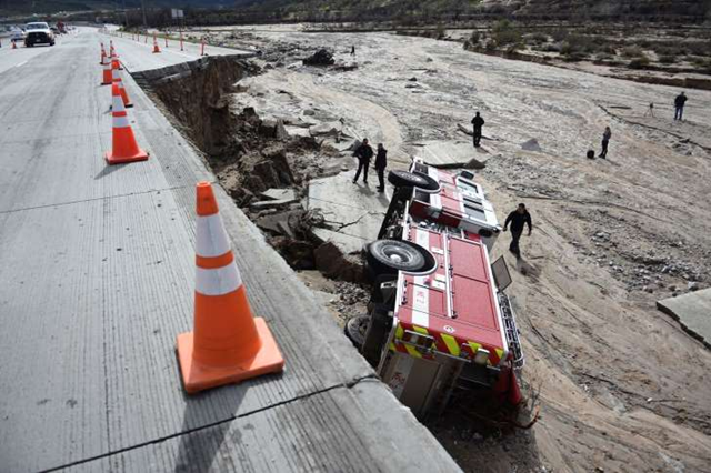 In this February 2017 photo, officials looked over the scene at Interstate 15 in the Cajon Pass, California, where part of the freeway collapsed due to heavy rain. Photo: The Associated Press