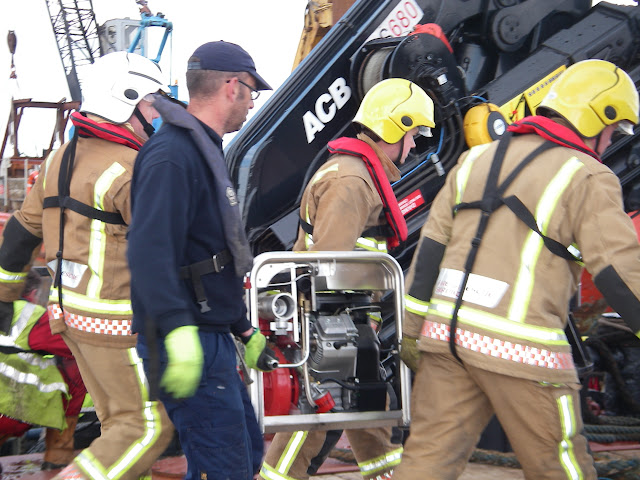 20 April 2012 - Firefighters and PHC personnel unload pump onto Green Island. Photo: RNLI/Poole Lifeboat Station Anne Millman