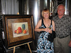 Artist Sheilah Unger and husband David with her donated painting which sold in the silent auction.