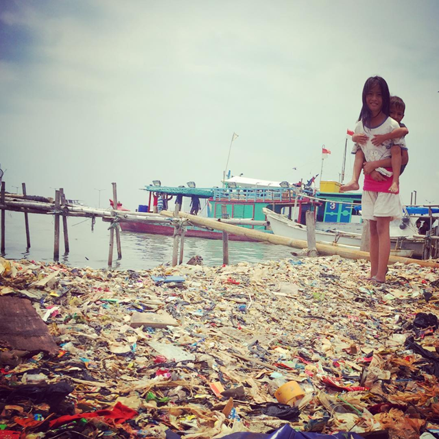 Aena, 12, in her village (Muara Angke) by Jakarta, 3 October 2016. The shoreline is smothered by plastic filth. This is what your backyard can look like if you're one of the 3.5 billion humans who don't receive trash pick-up services. Photo: bkkapologist / Instagram