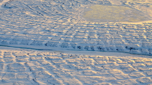 Winter sun setting over the tundra polygons in northern Alaska in November 2015. As winter sets in and snow settles, the soils take time to freeze completely and continue to emit carbon dioxide long into the new year. Photo: Charles Miller / NASA / JPL-Caltech