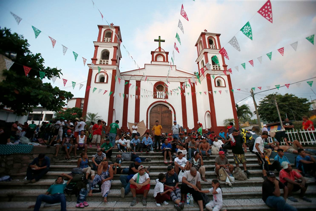 Central American migrants rest on the steps of a Catholic church in Pijijiapan, in southern Mexico, as a thousands-strong caravan that is slowly making its way toward the U.S. border stops for the night Thursday, 25 October 2018. Photo: Rebecca Blackwell / AP