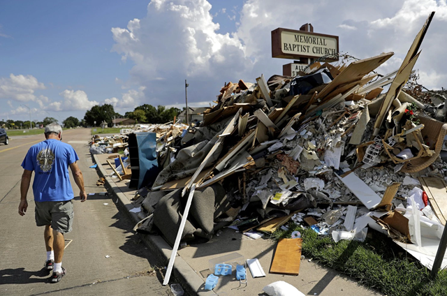 "Wayne Christopher walks by a pile of debris outside the church he'd attended his whole life damaged from Hurricane Harvey in Port Arthur, Texas, Monday, 25 September 2017. He and his wife had come here every Sunday and every Wednesday for more than four decades. This church is where he was baptized, where he met his high school sweetheart, then married her 46 years ago. ""We have a lot of memories here. This is my home. I've been here all my life,"" said Christopher. Photo: David Goldman/Associated Press"