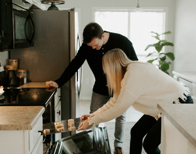 man watches while woman places cookie sheet into the oven