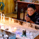 Kid lighting candles at cathedral in Cuenca