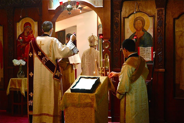 Subdeacon Nilus tends the candles during the Augmented Litany.