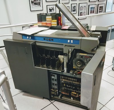 The IBM 1402 card reader at the Computer History Museum. Cards are loaded into the hopper on the right. The front door of the card reader is open, revealing the relays and other circuitry.