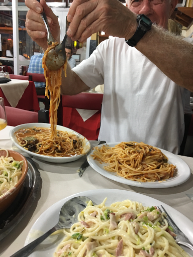 man dishing up pasta in a restaurant