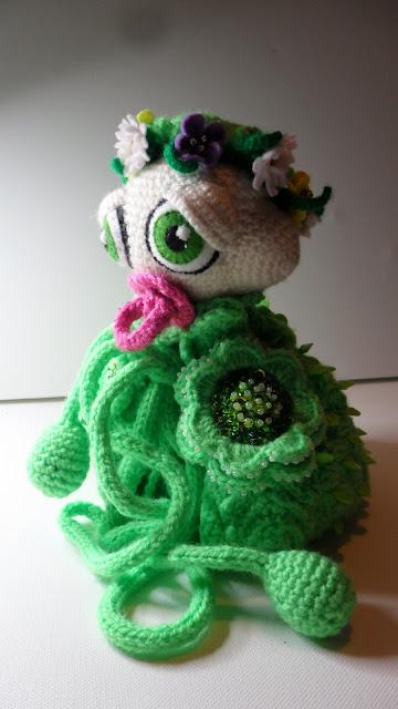 Cute Amigurumi crochet baby caterpillar, with beautiful big manga eyes, she looks sleepy. It has felt flower garland around it's head. Bright green body with Irish Crochet flowers, the flower are full beadwork, she has a bright pink dummy. Pompoms tie under her neck