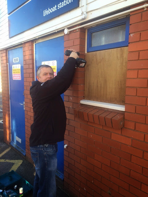 Volunteer crew member boards up the broken window at the station.  Unfortunately it will cost funds to fix the window properly.    It turned out to be a busy day on the water too for the crew with two separate shouts.  6 December 2014.