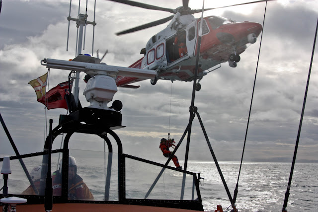 9 October 2011. Portland Coastguard helicopter prepares to lower its winchman onto the aft deck of Poole lifeboat while Coxswain Jon Clark maintains a steady course. Photo: Poole RNLI/Ade