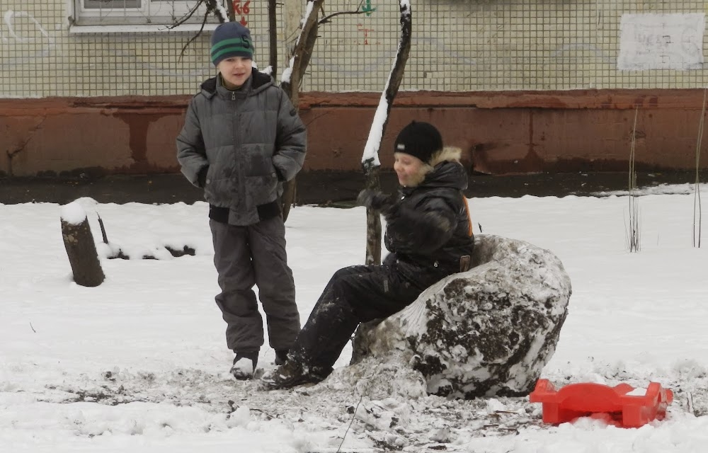 some kids playing outside in the fresh snow... though their self-made 'snow chair' doesn't look so fresh!