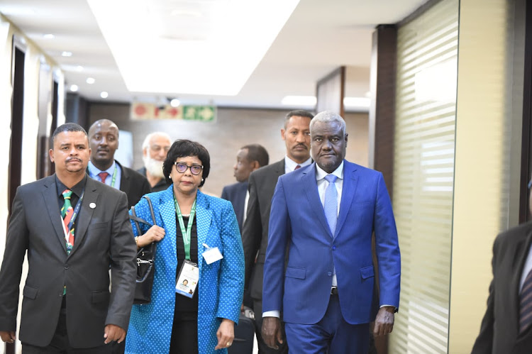 AU Chair Moussa Faki Mahamat, wearing a blue suit, arrives at the OR Tambo International Airport on Friday.