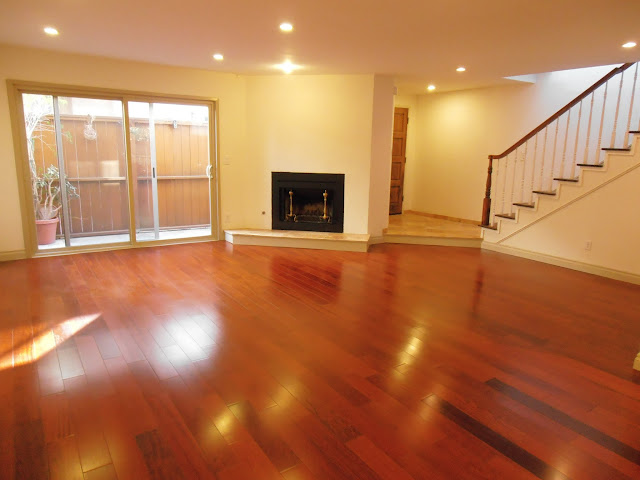 Large living room with recessed lights and fireplace
