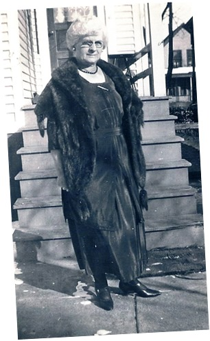 Copy of Gould_Mae Thorp_full shot wearing fur stole in front of steps_enh