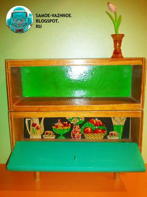 Шкаф для кукольного домика СССР деревянный старый советский. Игрушечный шкаф СССР нарисованный задник деревянный кукольная мебель чёрный фон посуда ваза яблоки виноград фрукты печенье конфеты цветы в вазе. Кукольный шкаф СССР с нарисованной посудой, вазой, яблоками, фруктами, виноградом, печеньем, конфетами, цветами чёрный фон картон игрушечная мебель для кукол деревянный сервант. Игрушечный шкаф СССР нарисованная посуда СССР чёрный фон сервант