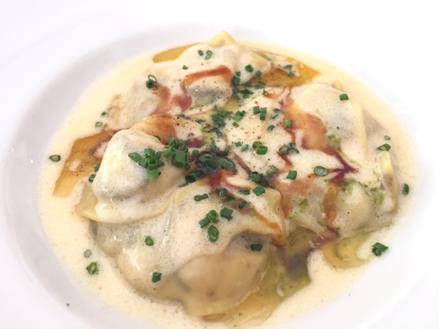 Homemade ravioli stuffed with mushrooms and prawns covered in parmesan sauce