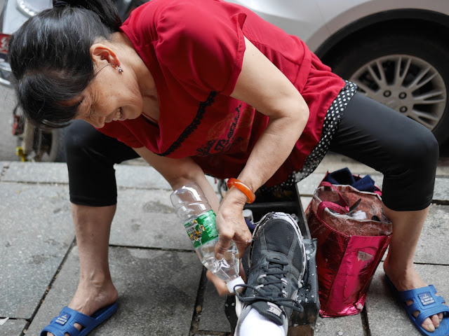 woman smiling as she cleans a sneaker