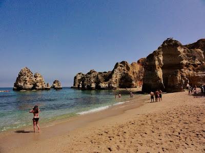 Stranden fra bakkenivå. Sand og sjø for forgrunnen, høye klipper i bakgrunnen.