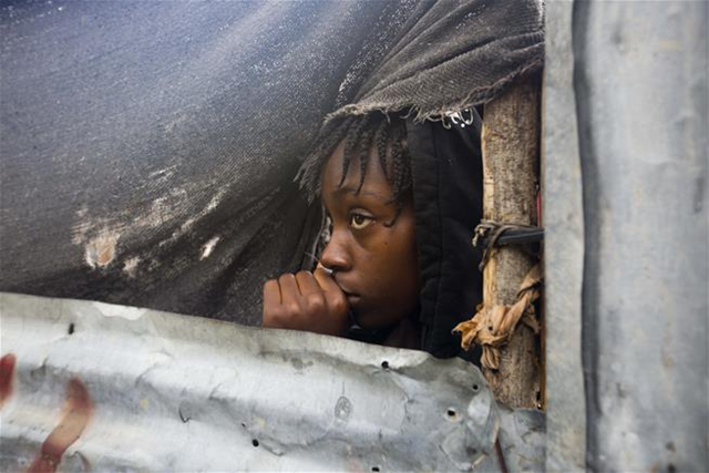 A girl watches as authorities arrive to evacuate people from her house in Tabarre, Haiti, Monday, 3 October 2016. Photo: Dieu Nalio Chery / AP Photo