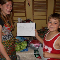 Meredith and Josh holding the Dawn Treader picture she drew for him for Christmas.