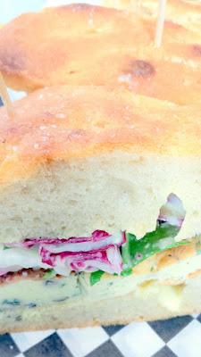 Frittata Sandwich with five herb frittata, housemade foccacia, arugula, radicchio, endive, lemon vin, aioli, pecorino