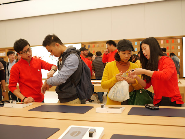 Apple employees assisting customers