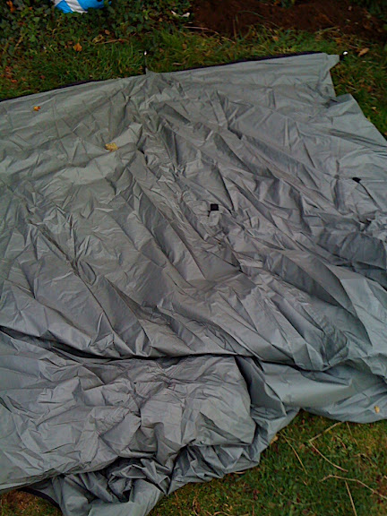 "The tent laid out on the ground. The useful ""pitching guide arrived with the order by email as a word document (to save the environment): very simple but valuableinstructions. 1. Peg out the grounsheet (black) first, but loosely. 2. Insert your uprights - can be paddles if canoeing, or walking poles or just sticks from your campsite."