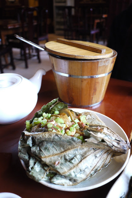 vegetarian dish in front of a wooden bucket of rice in Guiyang, Guizhou