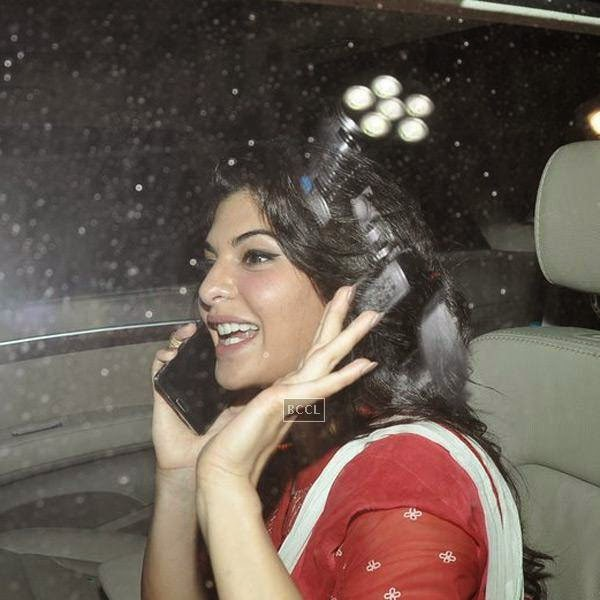 Jacqueline Fernandez talks on phone as she arrives for the screening of a movie, in Mumbai, on July 24, 2014. (Pic: Viral Bhayani)<br />