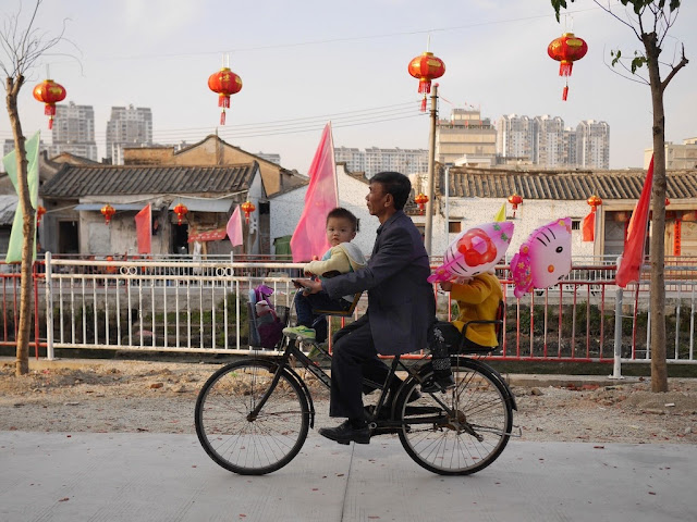 man riding a bicycle with children in seats in the front and back in Jieyang