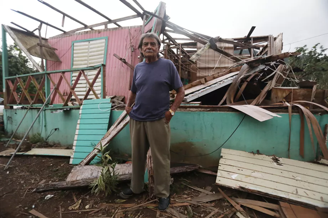 A man stands in front of his wrecked home in Utuado, Puerto Rico, on 19 December 2017. Photo: Mario Tama / Getty Images