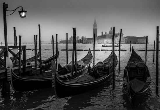 Venice, Italy. Popular view with Venetian gondolas in foreground and San Giorgio Maggiore island in the background at an overcast rainy day.