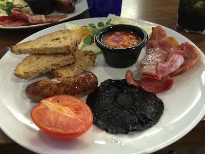 En tallerken med egg, bacon, bønner, toast, pølse, sopp og stekt tomat.