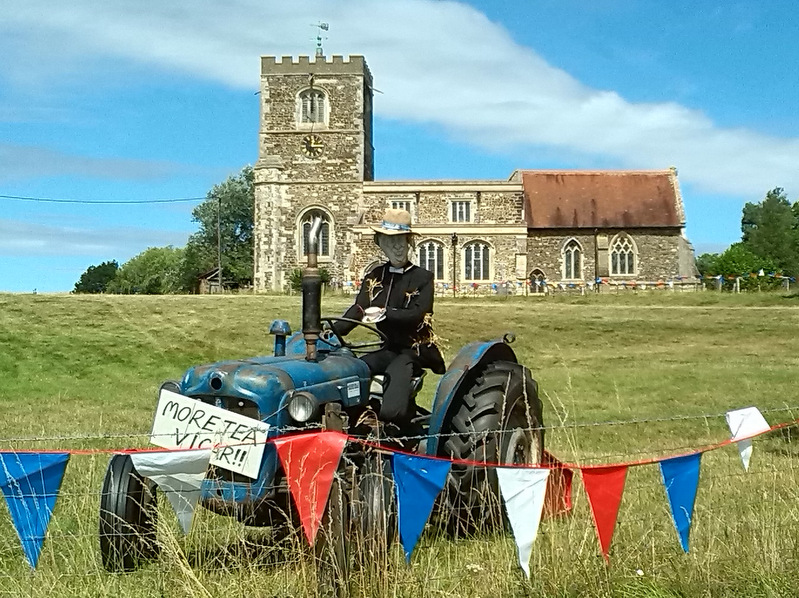 Scarecrow vicar holding teacup on a tractor