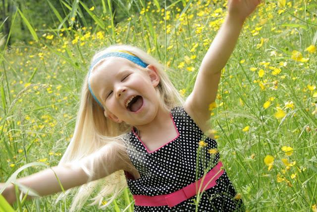 Happy girls dancing in a field of buttercups / Credit: Melanie LaVergne