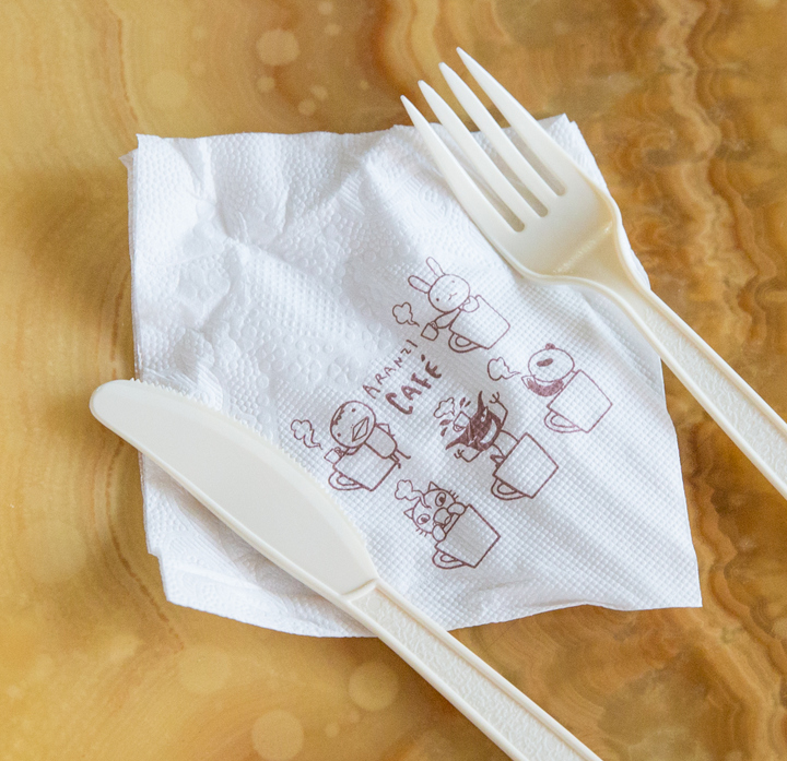 overhead photo of a napkin with a plastic fork and knife