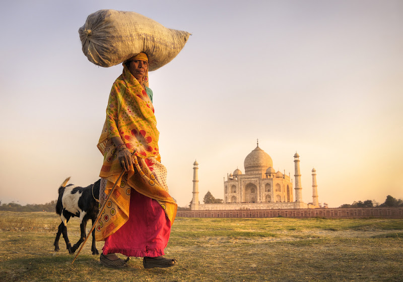 Taj Mahal in the background with an indian woman walking
