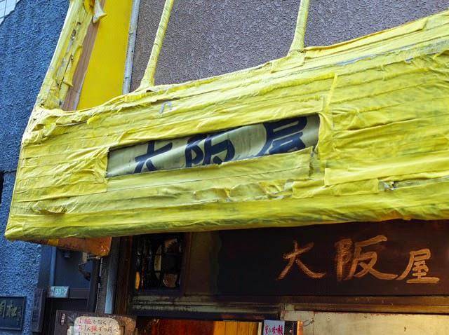 テント補修で半分隠れかかってる店頭の看板